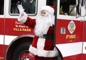 Santa riding his sleigh which is a fire truck